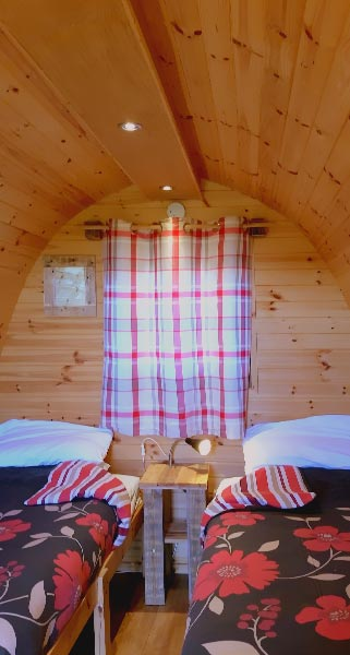 Two floral dressed beds inside Glamping Pod with the curtains closed