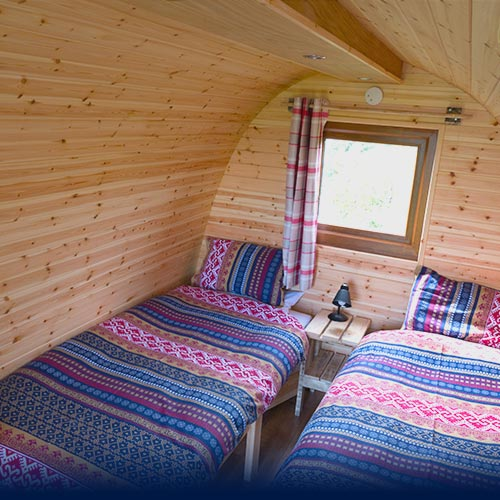 Two Scandinavian dressed beds inside Glamping Pod with porthole window above